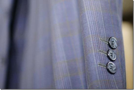 ジャケットの袖、青い練りボタン