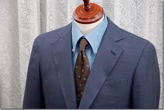 水色のデニムシャツに紺のジャケットとブラウンのネクタイ