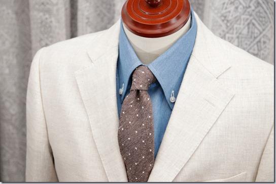水色のデニムシャツにアイボリーのジャケットと薄茶のネクタイ
